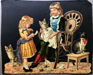 1890s large complex die-cut of two girls administering medicine to a sick cat